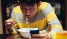 Japanese man eating noodles while reading